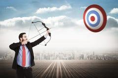 Составное изображение сфокусированного бизнесмена снимая лук и стрелы Стоковое Изображение