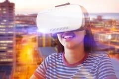 Составное изображение счастливой женщины смотря через имитатор виртуальной реальности Стоковое Изображение RF