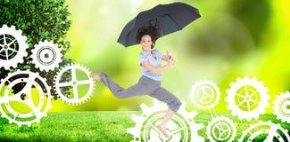 Составное изображение счастливой первоклассной коммерсантки скача пока держащ зонтик стоковое фото rf
