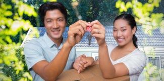 Составное изображение счастливых пар держа ключ дома и полагаясь на moving коробке стоковое фото rf