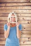 Составное изображение счастливого белокурого держа плана дома над стороной Стоковое Фото