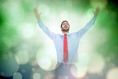 Составное изображение счастливого веселя бизнесмена поднимая его оружия стоковые фотографии rf