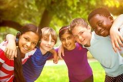 Составное изображение счастливых детей формируя груду на парке стоковое изображение