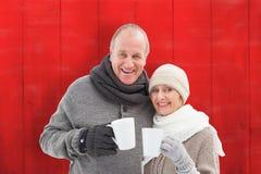 Составное изображение счастливых зрелых пар в зиме одевает держать кружки Стоковое Изображение