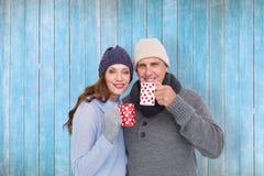 Составное изображение счастливых пар в теплой одежде держа кружки Стоковое Фото