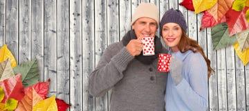Составное изображение счастливых пар в теплой одежде держа кружки Стоковая Фотография RF