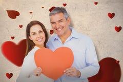 Составное изображение счастливых пар держа большое сердце формирует бумагу Стоковое Фото