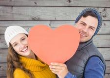 Составное изображение счастливых пар держа красное сердце Стоковые Фотографии RF