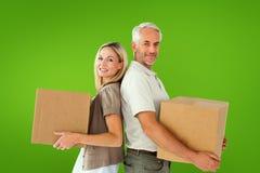 Составное изображение счастливых пар держа moving коробки Стоковое фото RF