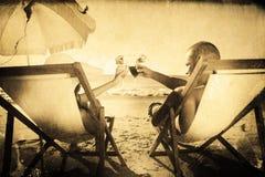 Составное изображение счастливых пар clinking их стекла пока ослабляющ на их шезлонгах Стоковая Фотография