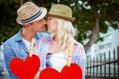 Составное изображение тазобедренных молодых пар целуя перилами Стоковые Фотографии RF