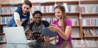Составное изображение творческой молодой команды дела смотря цифровую таблетку стоковое изображение