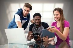 Составное изображение творческой молодой команды дела смотря цифровую таблетку Стоковое Фото
