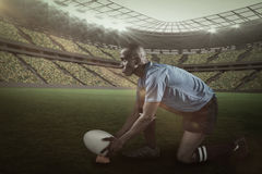 Составное изображение уверенно игрока рэгби смотря отсутствующий пока держащ шарик на пинать тройник с 3d Стоковая Фотография RF