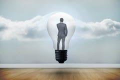 Составное изображение думая бизнесмена в электрической лампочке Стоковая Фотография RF