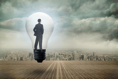 Составное изображение думая бизнесмена в электрической лампочке Стоковое Изображение