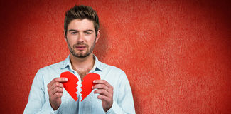 Составное изображение унылого человека держа половины сердца Стоковое Изображение