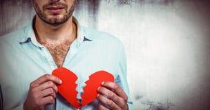 Составное изображение унылого человека держа половины сердца Стоковые Фото