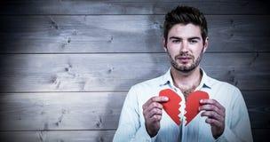 Составное изображение унылого человека держа половины сердца Стоковые Изображения RF