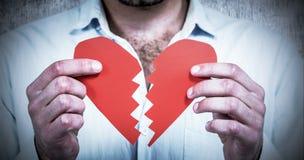Составное изображение унылого человека держа половины сердца Стоковое Изображение RF