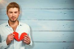 Составное изображение унылого человека держа половины сердца Стоковые Изображения