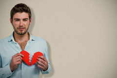 Составное изображение унылого человека держа половины сердца Стоковое фото RF