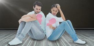 Составное изображение унылых пар сидя держащ 2 половины разбитого сердца Стоковое Изображение RF
