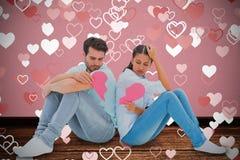 Составное изображение унылых пар сидя держащ 2 половины разбитого сердца Стоковая Фотография RF