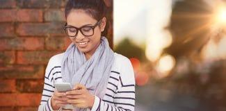 Составное изображение усмехаясь азиатской женщины используя smartphone Стоковые Фотографии RF