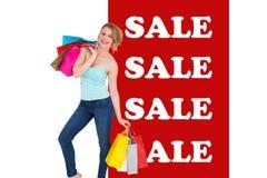 Составное изображение усмехаясь белокурой женщины стоя с хозяйственными сумками Стоковое фото RF