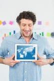 Составное изображение усмехаясь бизнесмена показывая цифровую таблетку в творческом офисе Стоковая Фотография RF