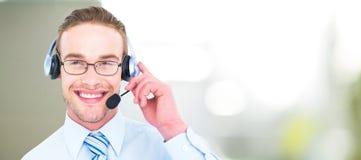 Составное изображение усмехаясь бизнесмена при шлемофон взаимодействуя Стоковое фото RF