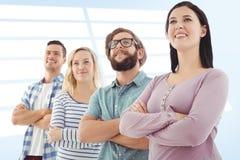 Составное изображение усмехаясь бизнесменов стоя в строке при пересеченные оружия Стоковое Изображение