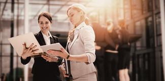 Составное изображение усмехаясь бизнес-леди используя цифровую таблетку Стоковое Изображение
