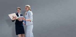 Составное изображение усмехаясь бизнес-леди используя цифровую таблетку Стоковое Фото