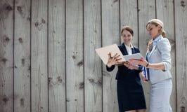 Составное изображение усмехаясь бизнес-леди используя цифровую таблетку Стоковая Фотография RF