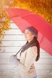 Составное изображение усмехаясь брюнет держа красный зонтик Стоковая Фотография RF
