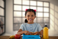 Составное изображение усмехаясь девушки имея сандвич на таблице Стоковые Изображения
