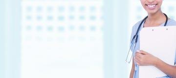 Составное изображение усмехаясь женского хирурга держа доску сзажимом для бумаги стоковые фото