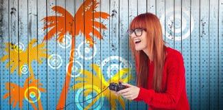 Составное изображение усмехаясь женщины битника играя видеоигры Стоковая Фотография