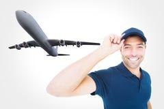 Составное изображение усмехаясь крышки работника доставляющего покупки на дом нося на белой предпосылке Стоковое фото RF