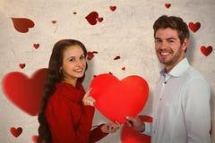Составное изображение усмехаясь пар держа бумажное сердце Стоковые Изображения RF
