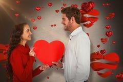 Составное изображение усмехаясь пар держа бумажное сердце Стоковые Изображения