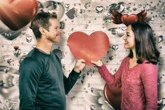 Составное изображение усмехаясь пар держа красное сердце формирует Стоковые Фото