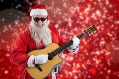 Составное изображение усмехаясь Санта Клауса играя гитару пока стоящ Стоковые Фотографии RF
