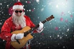 Составное изображение усмехаясь Санта Клауса играя гитару пока стоящ Стоковая Фотография