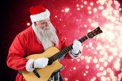 Составное изображение усмехаясь Санта Клауса играя гитару Стоковое Изображение