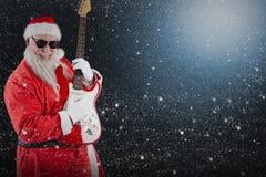 Составное изображение усмехаясь Санта Клауса играя гитару Стоковая Фотография