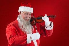 Составное изображение усмехаясь Санта Клауса играя скрипку Стоковое Фото