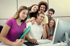 Составное изображение усмехаясь студентов в классе компьютера стоковое фото rf